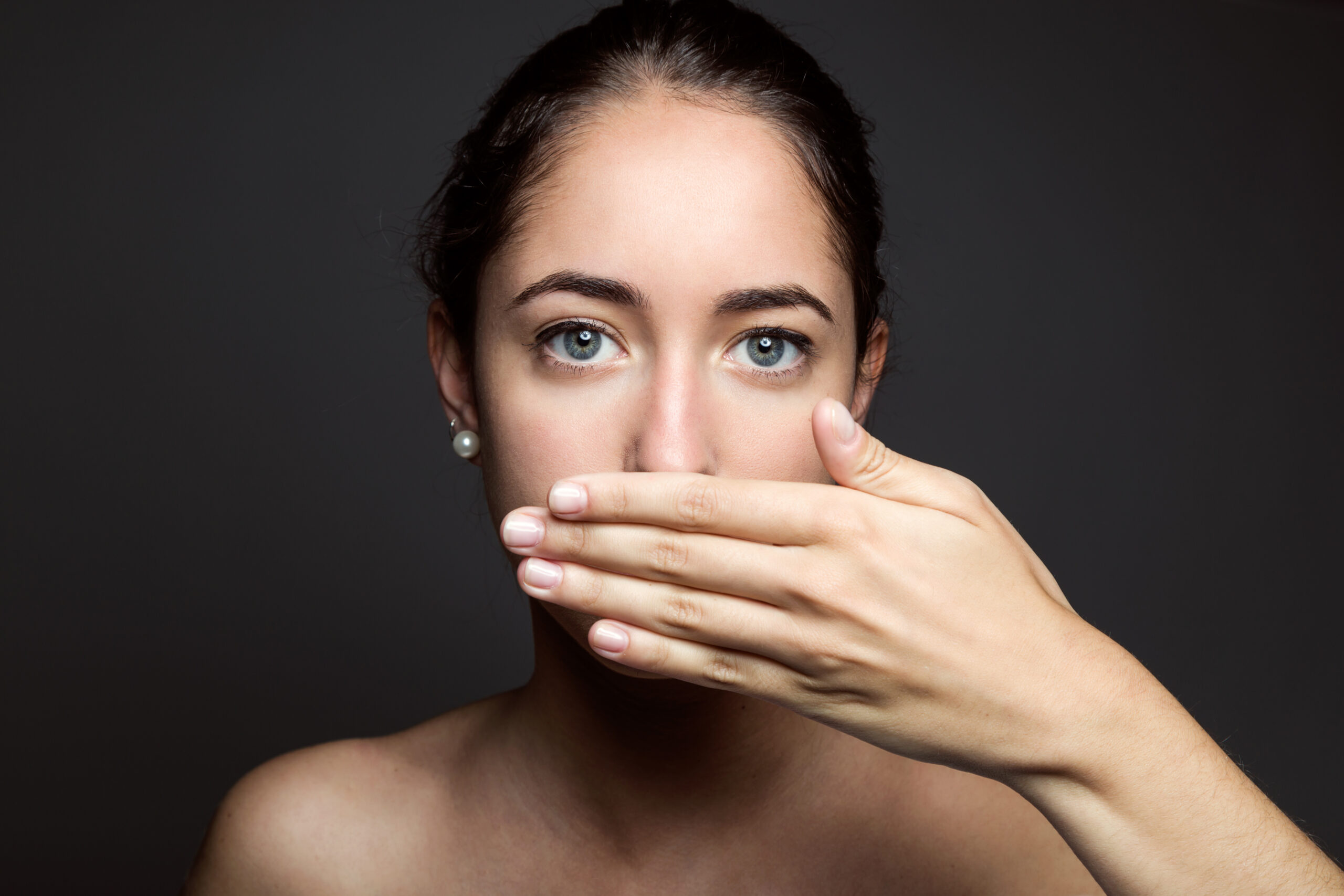 Beautiful young woman covering her mouth with hand. Isolated.
